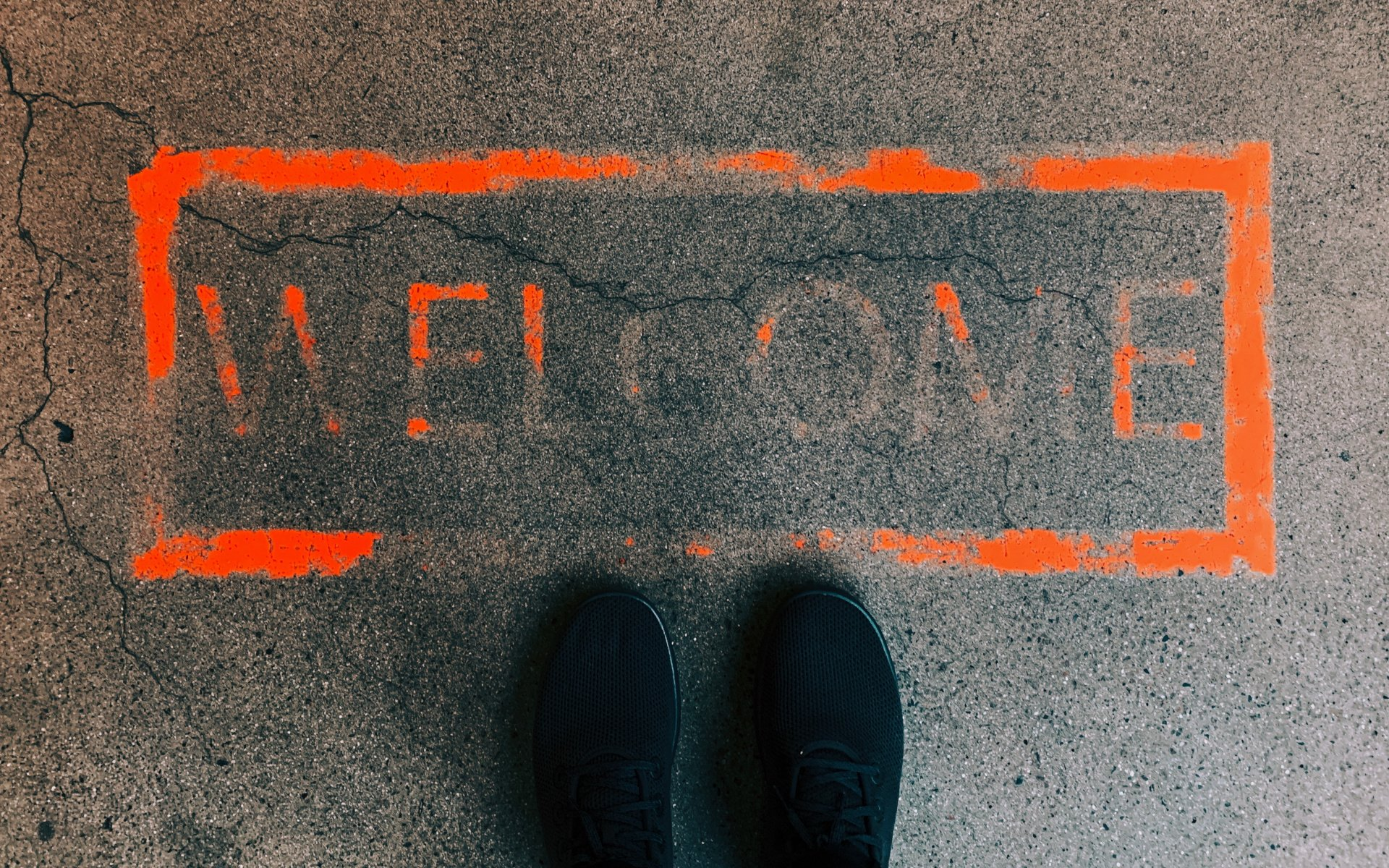 Welcome Wrote In Red Paint On A Concrete Floor With Black Shoes