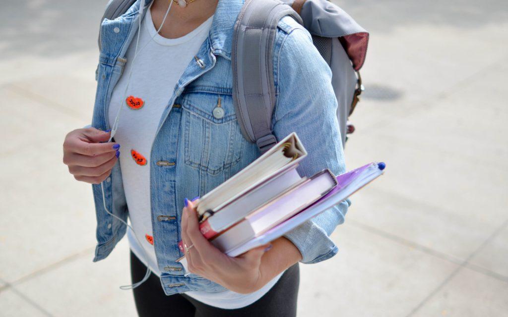 Woman Wearing A Blue Denim Jacket Holding Some School Books