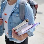 Woman Wearing A Blue Denim Jacket Holding Some School Books